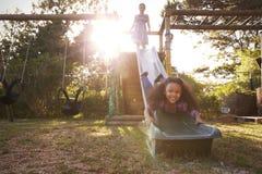 Deux filles jouant dehors à la maison sur la glissière de jardin Images stock