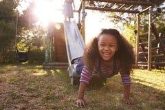 Deux filles jouant dehors à la maison sur la glissière de jardin Photographie stock libre de droits
