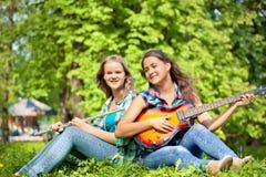 Deux filles jouant la guitare et la cannelure en parc Image stock