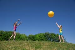 Deux filles jouent avec la bille jaune Photographie stock libre de droits