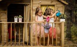 Deux filles jouent avec la boîte d'arrosage dans une cabane dans un arbre Photo stock