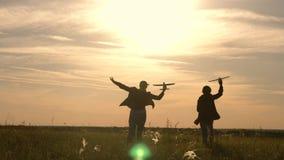 Deux filles jouent avec un avion de jouet au coucher du soleil Enfants sur le fond du soleil avec un avion ? disposition Silhouet banque de vidéos