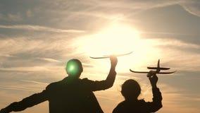 Deux filles jouent avec un avion de jouet au coucher du soleil R?ves du vol concept d'enfance heureux Enfants sur le fond du sole banque de vidéos