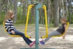 Deux filles jouent sur le terrain de jeu sur l'attraction en métal jaune Il est venteux photo libre de droits