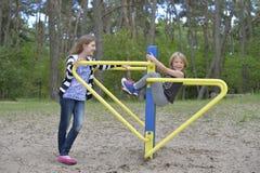 Deux filles jouent sur le terrain de jeu sur l'attraction en métal jaune Il est venteux photo stock