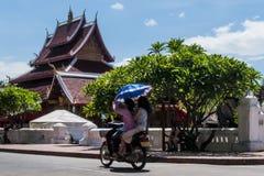 Deux filles laotiennes montent un scooter devant le temple de Wat Mai Suwannaphumaham dans Luang Prabang, Laos, tenant un paraplu photos libres de droits