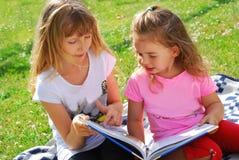 Deux filles lisant un livre dans le jardin Photographie stock