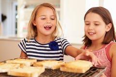 Deux filles mangeant du fromage sur le pain grillé dans la cuisine Image stock