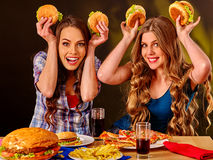 Deux filles mangeant du prêt-à-manger en café photographie stock