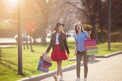 Deux filles marchant avec des achats sur des rues de ville Images libres de droits