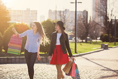 Deux filles marchant avec des achats sur des rues de ville Photo stock