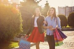Deux filles marchant avec des achats sur des rues de ville Photo libre de droits