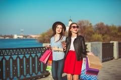 Deux filles marchant avec des achats sur des rues de ville Photos stock