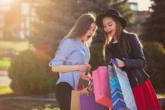 Deux filles marchant avec des achats sur des rues de ville Photographie stock