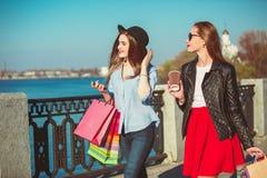 Deux filles marchant avec des achats sur des rues de ville Photographie stock libre de droits