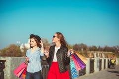 Deux filles marchant avec des achats sur des rues de ville Image stock