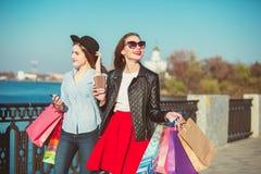 Deux filles marchant avec des achats sur des rues de ville Images stock