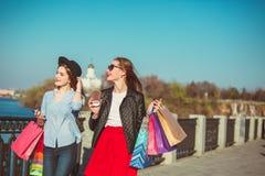 Deux filles marchant avec des achats sur des rues de ville Photos libres de droits