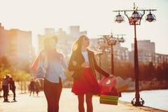 Deux filles marchant avec des achats sur des rues de ville Image libre de droits