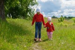 Deux filles marchant le long du chemin tenant des mains image stock