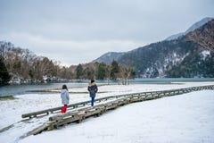 Deux filles marchant sur la promenade par le lac dans la neige Photo libre de droits