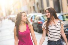 Deux filles marchant sur la rue tenant des mains Photos stock