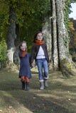 Deux filles marchant sur un chemin dans le bois Image stock