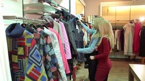 Deux filles marchent dans un magasin d'habillement, elles regardent des v?tements et les essayent banque de vidéos