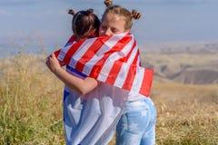 Deux filles mignonnes avec les drapeaux américains et israéliens photo libre de droits
