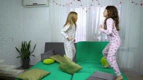 Deux filles mignonnes dans des pyjamas dansant sur le sofa clips vidéos
