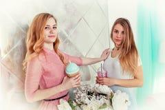 Deux filles mignonnes dans des robes boivent des boissons des tasses avec des couvercles et t Photo stock