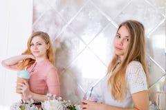 Deux filles mignonnes dans des robes boivent des boissons des tasses avec des couvercles et t Photographie stock