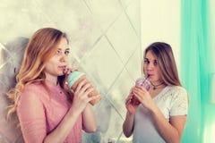 Deux filles mignonnes dans des robes boivent des boissons des tasses avec des couvercles et t Images stock