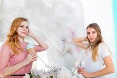 Deux filles mignonnes dans des robes boivent des boissons des tasses avec des couvercles et t Images libres de droits