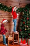 Deux filles mignonnes de petit enfant décore l'arbre de Noël à l'intérieur image stock
