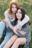 Deux filles mignonnes s'asseyant sur l'herbe Images stock