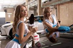 Deux filles minces sexy dans le style de la formule 1 à la lave-auto photographie stock