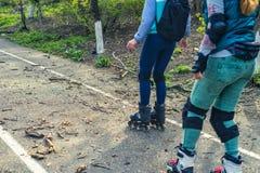 Deux filles montent sur des rouleaux sur une route très mauvaise Images libres de droits