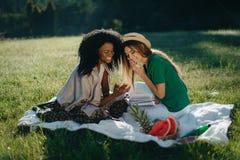 Deux filles multi-ethniques ont l'amusement sur le pique-nique La jeune fille africaine avec du charme montre sonething drôle sur Photo stock