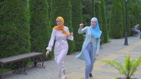 Deux filles musulmanes de sourire positives dansant dans la rue banque de vidéos