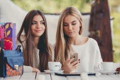 Deux filles observent des photos sur le smartphone Image libre de droits