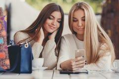 Deux filles observent des photos sur le smartphone Images libres de droits