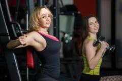 Deux filles pèsent la formation dans le gymnase Image libre de droits