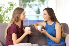 Deux filles parlant et buvant à la maison Photos libres de droits