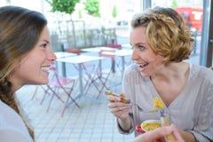 Deux filles parlant et souriant pendant la pause de midi Photographie stock