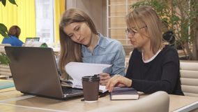 Deux filles passent en revue un certain journal au hub fonctionnant images stock