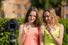 Deux filles pendant l'été en parc Été en nature Jeunes bloggers d'amies montrant des gestes des mains CORRECT sourires Photos libres de droits