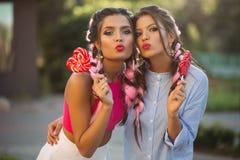 Deux filles posant et faisant le duckface avec le coeur de sucreries sur le bâton Images libres de droits