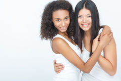Deux filles positives embrassant étroitement Image stock