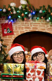 Deux filles près de la cheminée et de l'arbre de Noël Photo libre de droits